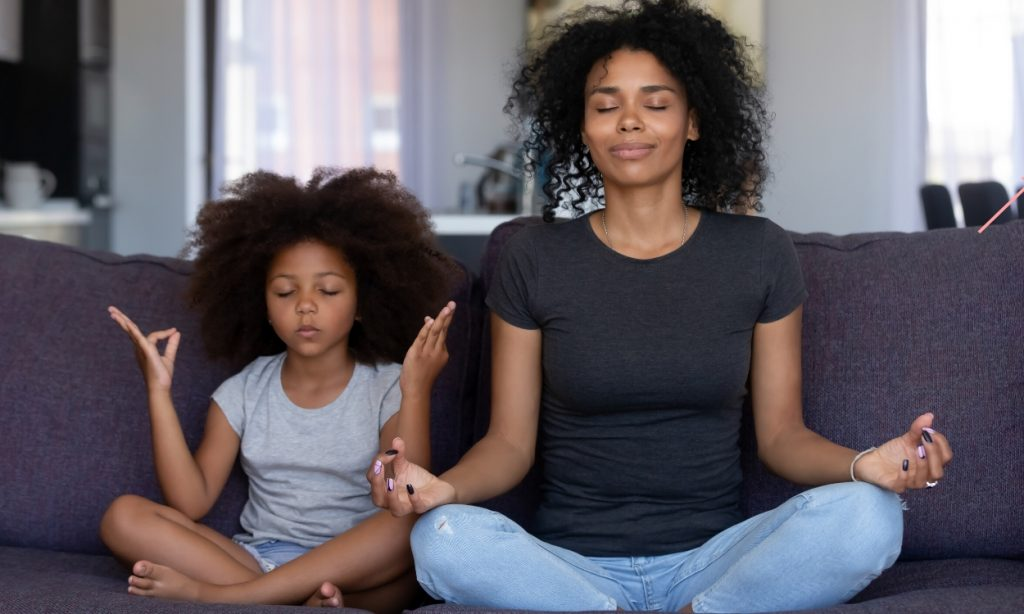african american mom and daughter with eyes closed taking deep breaths