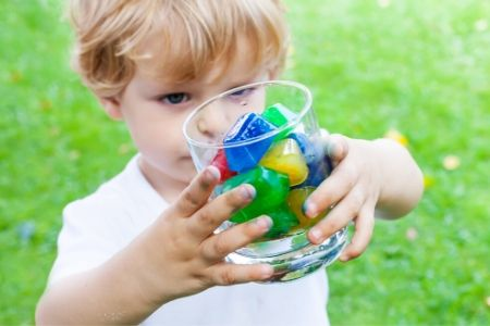 Blonde kid with colorful ice cubes in a glass