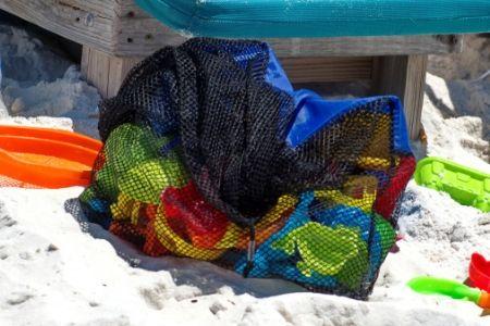 Mesh beach bag full of beach toys