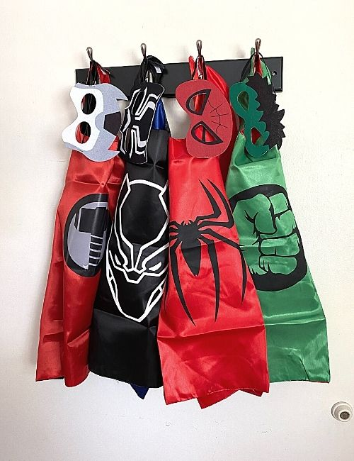 Superhero capes hanging on the coat rack