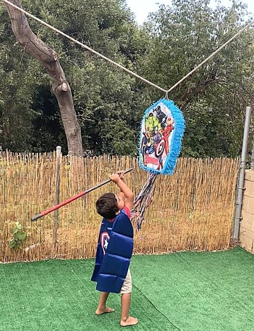 Kid with brown hair swinging at an Avengers themed pinata